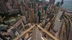 A 17-year-old daredevil captures stomach-churning footage on his GoPro camera on Aug. 11, 2014, after scaling a Hong Kong skyscraper with no safety equipment. (Caters News Agency)