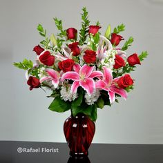 Fragrant stargazer lilies and red rose arranged in a rubby red vase.