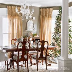 Graceful white reindeer figurines introduce a sophisticated woodlandtablescape. A statuesque tree sparkles with a stunning assortment ofglitterywhite, silver, and gold ornaments and accessories. Limiting the color scheme keeps the focus on the room's elegant design. /