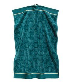 Petrol. Handtuch mit Jacquardmuster auf der Veloursoberseite. Rückseite aus Frottee. Das Handtuch hat einen goldfarbenen Streifen an den Enden. Schlaufe