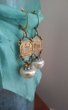These vintage assemblage earrings feature antique glass baroque pearl buttons. For the centerpiece of these lovelies I used charms from an