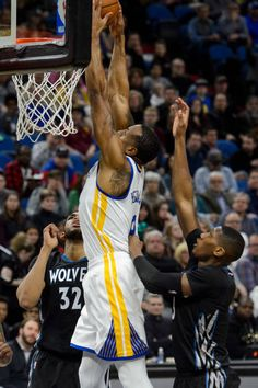 Andre Iguodala of the Golden State Warriors shoots the ball against KarlAnthony Towns and Kris Dunn of the Minnesota Timberwolves during the second...