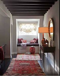 layered area rugs, beamed ceilings and a cozy bench
