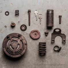 Still life imagery including rusty car parts on a concrete floor in the garage.