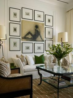 An art wall over a classic white sofa features small double-matted prints in slim black frames and one central artwork.