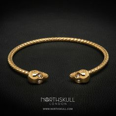 Our Gold Faceted Twin Skull Bangle is handcrafted with meticulous attention to detail. Featuring an open design with a precision cut clear Swarovski crystal set in each eye, the 18kt. Gold finish makes this a sleek & stylish addition to the wrist | Available now at Northskull.com [Worldwide Shipping] #Luxury #Jewelry #MensFashion