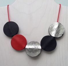 KOTA Silver-Red-Black Necklace by Klara Borbas. Five polymer discs on red waxed cotton cord with a large stainless steal clasp. One side of the discs is covered with silver leaf, the other side is red or black. It gives a wide variety of mixing colors or wear it monochrome.