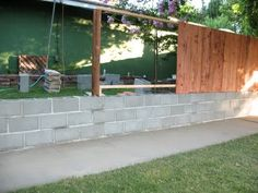 Exactly what I want for our backyard.  Cinder blocks with fence on top.  Build out garden beds so I can easily get to the beds.