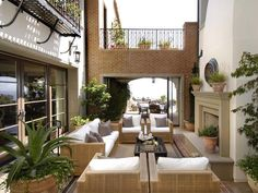 A porthole mirror and potted plants dress up this outdoor fireplace courtyard... gorgeous!