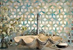 Jewel glass mirror mosaic tile in a sacred geometry pattern (flower of life) serves as the perfect background for a shell shaped sink.