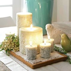 Your Christmas dinner table will sparkle with a collection of candles covered in a dusting of faux flurries. To make the decoration for Christmas, pour Epsom salts onto a flat surface. Sprinkle glitter on top; mix. Apply a layer of decoupage adhesive to the lower half of white pillar candles using a paintbrush. While wet, lay the candles in the salt-glitter mix. Lift, rotate, and repeat until all sides are covered./