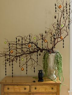 Create an eye-catching #Halloween arrangement from fallen branches in an old urn draped with Spanish moss. Spray-paint old Christmas ornaments and beaded trims to hang.