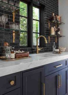 designed by architect Wilson Fuqua, with interiors by Theresa Rowe. love the contrast in this kitchen. white grout keeps the black tile from overpowering and the gold accents really make the space pop.