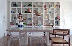 A arquiteta Gabriela Marques desenhou a estante de laca branca, elemento marcante da decô, que guarda objetos trazidos de viagens e heranças de família. A mesa é da mesma cor e as cadeiras transparentes reforçam a claridade do ambiente