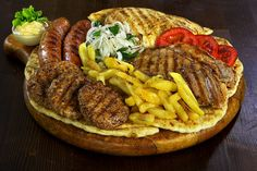 """For our meat lovers, our signature """"pikilia""""* offers a selection of meats - traditional meatballs, lamp cutlets, pork steaks, chicken filets, locally made """"village"""" sausages - all served with pita bread, hand cut fries, tsatsiki, salad and feta cheese balls.  *All our meats are locally sourced"""
