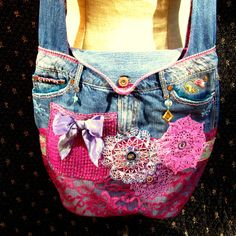 This is a one of a kind upcycled demin messanger bag/purse.    This is a roomy and strong denim bag. The bottom is oval shaped and reinforced to carry a lot. The bag was a cute pair of womens jeans. The leg fabric is not the over the shoulder strap that is wide for comfort. The lower half of the bag is covered with magenta colored lace fabric. On the front there is a wide floral ribbon on the lace. On top of that are two hand dyed doilies in lilac and purple. The third doily was hand tinted…