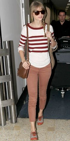 Taylor Swift in striped sweater, colored jeans, leather satchel, Oxford shoes, and Ralph Lauren shades