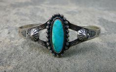 This Fred Harvey tourist cuff has a lovely turquoise stone set in a plain bezel and surrounded by drops. Applied 'mountains' adorn the sides and the piece is completed with traditional Harvey stamps on the sides.