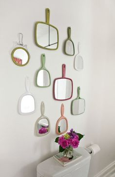 Paint the plastic of a cheap handheld mirror and hang on the wall in each girl's room or playroom?