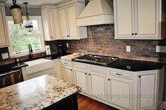 brick backsplash, island, apron sink, light above sink