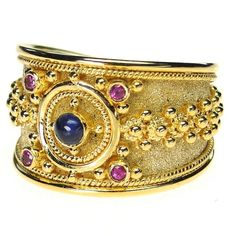 Materials 18k Gold, Rubies and a choice of Sapphires (name your color!). Specifics The face is approx 5/8 inch wide. The ring will be made to your size by the designer for a perfect fit.
