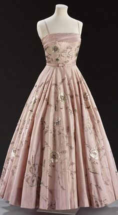 A 1955 Worth London dress in pink silk with crystal embellishment, created when Owen Hyde-Clark was chief designer. Cut as a circle, the piece would have required many petticoats for full effect.