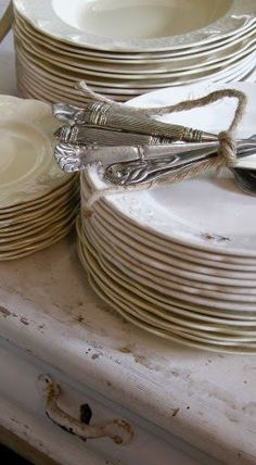 Love this look.  Plates placed upon vintage white suitcase and silverware tied with twine.