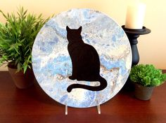 Black cat silhouette on vinyl record, with pour painting abstract background.