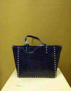 Bolso en azules con tachuelas y asas cortas. Muy combinable