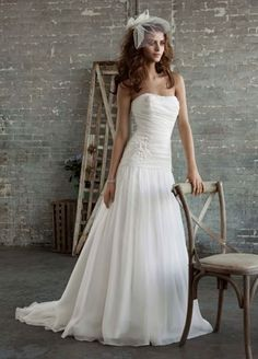 Timeless and romantic, this organza slim gown is effortlessly beautiful.  Strapless bodice frames the neck and shoulders while the drop waist creates a flattering shape.  Floral appliques adorn the soft organza for a look that is ethereal and feminine.  Chapel train.  Fully lined. Back zip. Dry clean only.  Available online in Soft White.