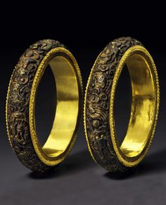 China | Pair of Chenxiangmu wood (aloeswood / agarwood) bangles; outer surface of each is carved in relief with four dragons emerging from clouds, with the details picked out in gold inlay, and bordered on either side with a narrow beaded gold band. The interiors of the bangles are mounted in gold sheet. | ca. Late Qing Dynasty | 137'000$ ~ sold (March '15)