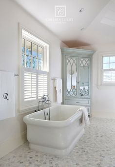 Fabulous bathroom features freestanding bathtub paired with wall-mounted tub filler situated under window dressed in plantation shutters situated next to corner armoire painted turquoise accented with mirrored doors atop calacatta michaelangelo marble tiles.