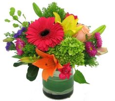 This vibrant arrangement is sure to lift spirits with bright and bold colored gerber daisy, rose, hydrangea, lillies, and crown asters accented with seasonal greens