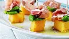 Blanda melon med lite olivolja och krydda med svartpeppar. Lägg upp på fat och lägg basilika och prosciutto på melonbitarna och stick i små grillspett av trä. Ringla över extra olivolja och krydda med svartpeppar.