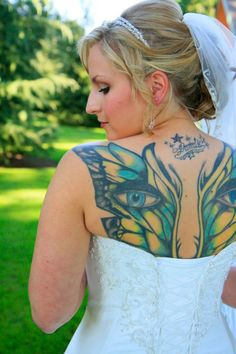 Bride showing off an epic tattoo on her wedding day instead of trying to cover it up.