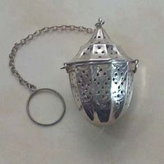 Sterling tea ball infuser with hinged lid and attached chain and ring, which bears the Webster Company mark.