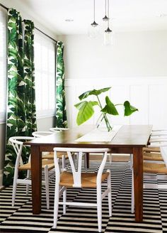 Gorgeous pairing of stripes and tropical banana leaf print in this contemporary dining room.