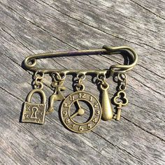Antique bronze kilt pin brooch in a steampunk style with 5 dangling charms. Large safety pin brooch with 5 loops filled with charms. #sunnydazestudio #Bexhill #steampunk #kiltpin #handmadejewellery #antiquebronze #steampunkjewellery #steampunkaccessories #kiltpinbrooch #steampunkbrooch #antiquebronzebrooch #bronzebrooch #charmbrooch #handmadebrooch #safetypinbrooch #largesafetypin #giantsafetypin #giftideas #broochgift #kiltpingift