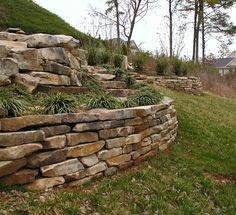 stacked fieldstone retention wall - i like the curves on this... and how it's tiered -
