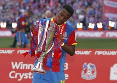 Crystal Palace's English striker Wilfried Zaha poses with the trophy following victory in the English Championship Play Off final football match between Crystal Palace and Watford at Wembley Stadium in London on May 27, 2013.  Crystal Palace won 1-0
