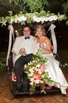 The bride and groom departed their wedding reception at The Grand Hotel in Point Clear, Ala. via a decorated golf cart. | Wedding Photography by Kelli + Daniel Taylor Photography   www.danieltaylorphoto.com