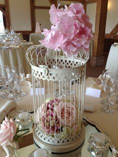 birdcage with internal posy of pink roses, carnations and eustoma with pink hydrangea detail