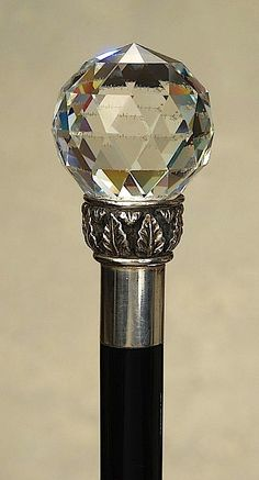 """A lovely faceted crystal cane. The large crystal ball handle is 1 7/8"""" in diameter. It is cut in diamond facets with a 1 1/8"""" concentric circle cut at the top. It sits on a silver base decorated with a ring of acanthus leaves. The thin lower ring is marked: """"925"""" along with worn Continental hallmarks. There is a 1"""" smooth silver collar on an ebony shaft that ends with a 1 1/3"""" gently worn brass ferrule.  It is ca 1900 and it is a fine decorative example."""