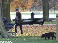 Princess Kate pushing Prince George in a Silver Cross Pram. She is wearing tight fit jeans, a jacket,  baseball hat and trainers.