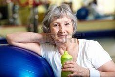 senior gymnastique: Portrait de femme âgée avec une bouteille d'eau par balle bleue