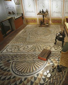 View of a reconstruction of a Roman living room. This reconstruction shows a living room of a wealthy London house in c300 AD. It is on show at the Roman gallery, Museum of London. The mosaic floor was found in 1869 during the reconstruction of Queen Victoria Street. The mosaic is made of various coloured cubes of stone and ceramic. It was revelead to the public in 1869. The reconstruction setting is of similar date and the wall painting is based on plaster fragments from Austin Friars.