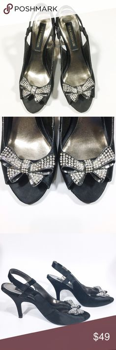 Steve Madden Luxe Black Satin Crystal Bow Heels Glamorous black satin peep toe heels from Steve Madden's Luxe Collection. Stunning and stylish silver crystal bows adorn the top. They easily slide and stay on with a strap that stretches around the back heel and doesn't require fastening. These gorgeous shoes are preloved and do show some signs of wear on the bottom soles (picture 6), and some scratches on one of the heels (picture 7). Otherwise they are in beautiful condition with no missing…
