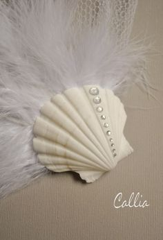 Love the idea with the seashell, not to crazy about the feathers thought