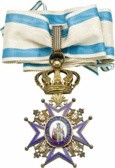 Serbian Silver-gilt and Enamel Order of Saint Sava  A Commander's neck badge, the silver-gilt ball-tipped cross decorated with blue-edged white enamel, small eagles in the angles between the arms, centering an oval portrait of the national Saint in red vestments, outer blue band is inscribed By His Talents­- 87.7 x 49 mm including crown suspender, with original ribbon in case of issue