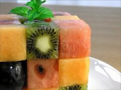Video tutorial. Rubik's Cube Fruit Dessert. Watermelon, cantaloupe, kiwi, and grapes. Use a square cutter as a guide. Brush each layer with a sugar water mixture (gelatin?).